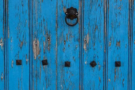 blue wooden door with black steel knocker