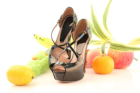 pair of black peep-toe platform pumps in middle of assorted fruits