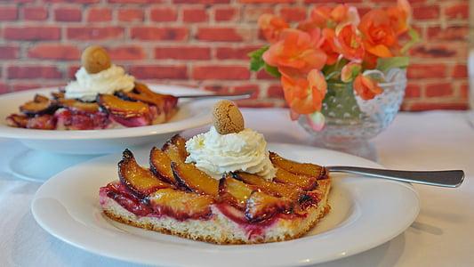 cake in white plate beside orange petaled flowers centerpiece