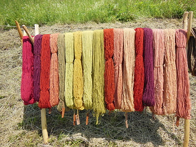 assorted-color thread hanging on wooden rack