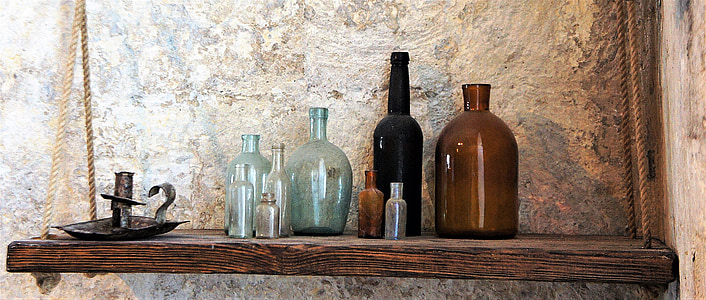 glass bottles on brown wooden floating shelf