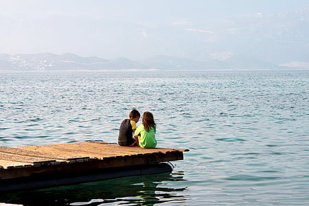 man and woman sitting on brown docking pier