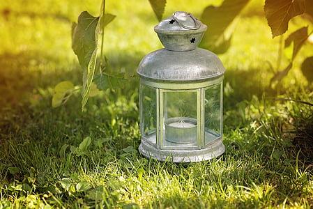grey candle lantern on green grass field