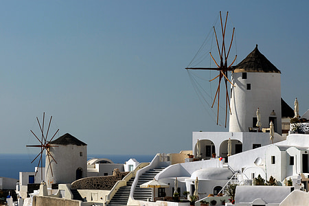 white painted buildings with windmill under blue sky at daytime