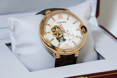 photo of round white Cartier mechanical watch with black leather strap and box