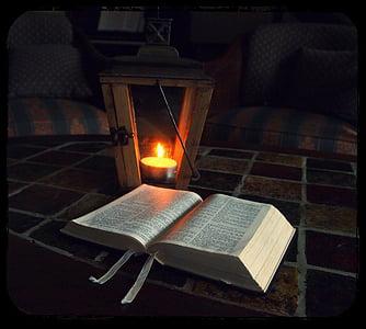 open book near candle lantern inside room