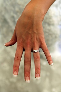 person wearing silver-colored bridal rings