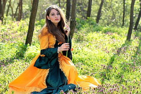 woman in orange and green long-sleeved dress sitting in the woods during daytime