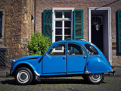 blue Citroen 2CV near brown wall bricks during daytime