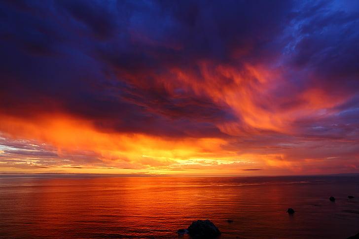 body of water under orange sky