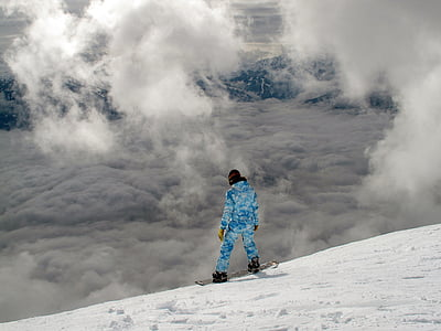 man in blue jacket and trouser on snowboard