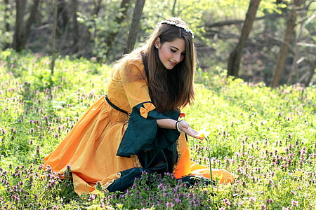woman touching flower at the field during day