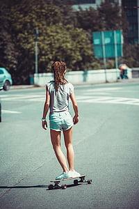 selective focus photography of girl wearing grey cap-sleeved shirt and blue denim shorts skateboarding