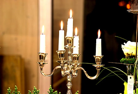 five white lighted candles on brown holder