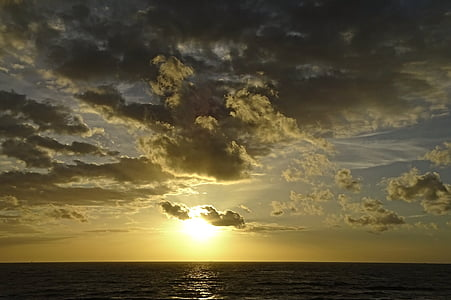 body of water at cloudy sky during sunrise