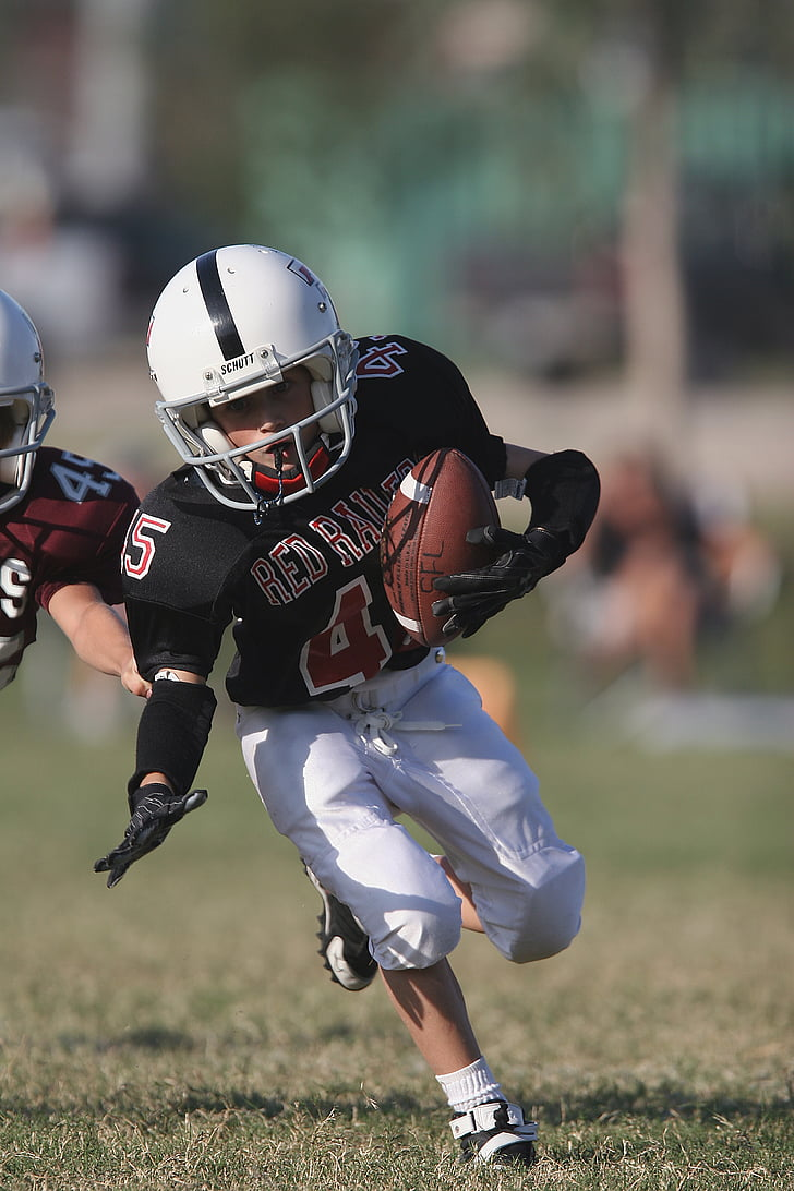boy defending football on the grass