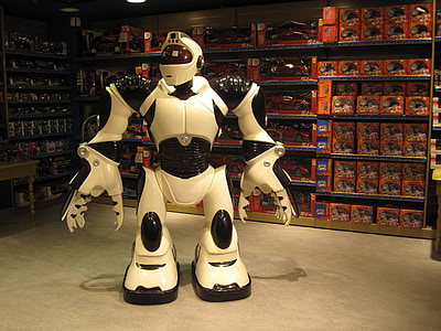 white and black robot standing next to grey muscle rack