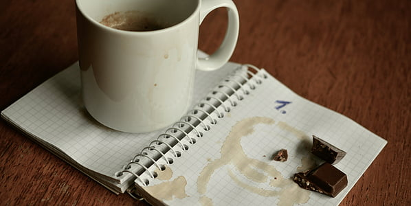 white ceramic mug and chocolate placed on notebook page