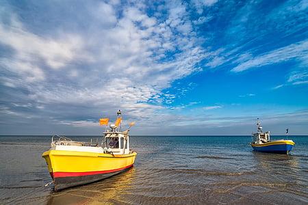 yellow and white fishing vessel on seashore