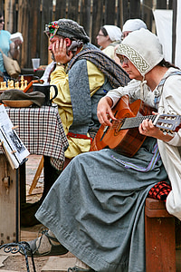 woman sitting on bench while playing guitar