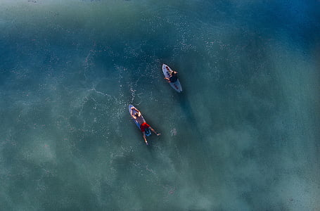 aerial photography of two male riding surfboards