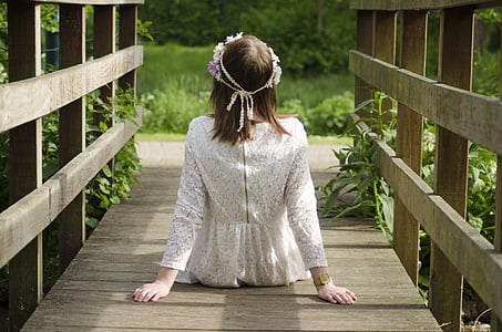 woman wearing white long-sleeved top sitting on brown wooden bridge