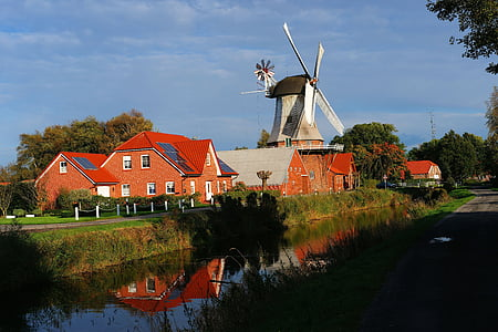 windmill beside river surrounded by trees