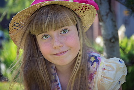 girl wearing brown sun hat smilling