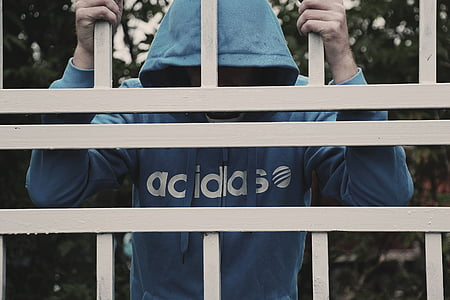person in blue adidas shirt holding gate bars
