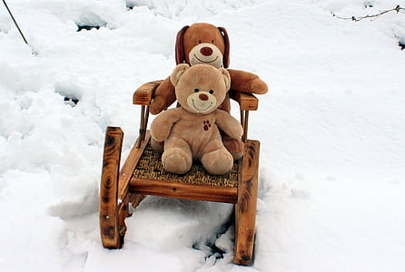 two brown bear plush toys riding sleigh