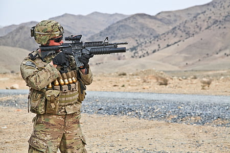 military man holding rifle in an open field