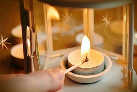 photo of white scented candle on gray steel candle holder