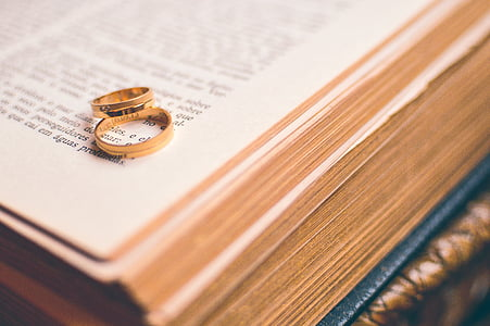 two gold-colored rings on open book