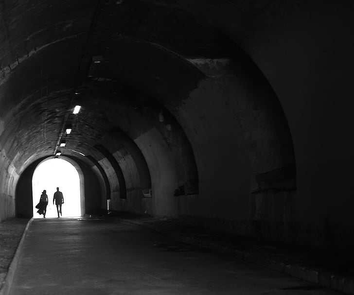 two person's silhouette in tunnel