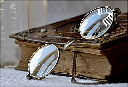 close-up photography of gold-colored frame eyeglasses on top of brown book