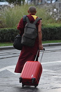 monk carrying bag while holding red luggage walking on road