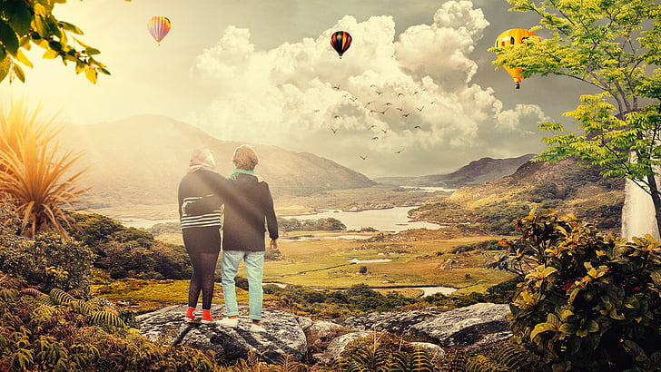 two women watching hot air balloons in sky