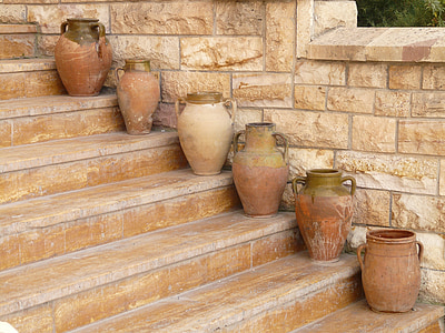 six brown clay pots on stairs