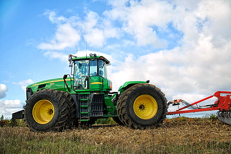green and yellow tractor with cultivator at daytime