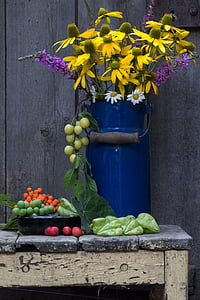 photography of yellow flowers in blue metal vase