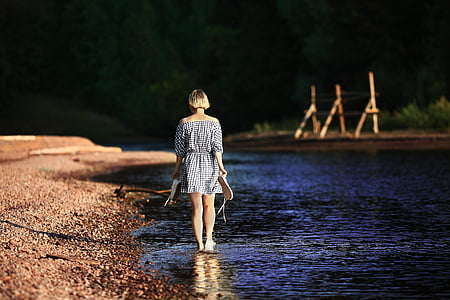 woman walking on body of water at daytime