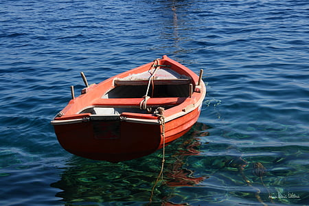 orange row boat on blue waters