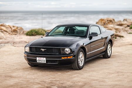 black Ford Mustang coupe beside body of water