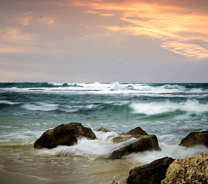 ocean waves bashing rocks on sea shore at sunset
