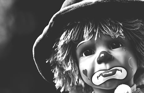 grayscale photo of sad clown