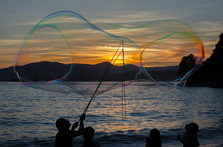 silhouette of man making large bubbles during sunset