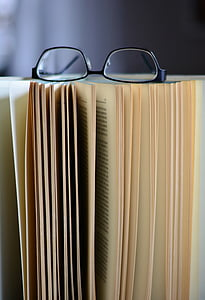 selective focus photography of opened book with eyeglasses on top of it