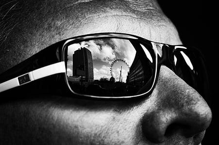 ferris wheel reflection on man's sunglasses