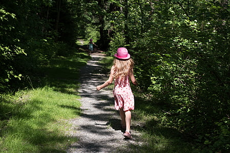 girl wearing pink hat running through forest