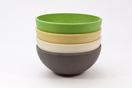four green, brown, beige, and gray bowls on white surface